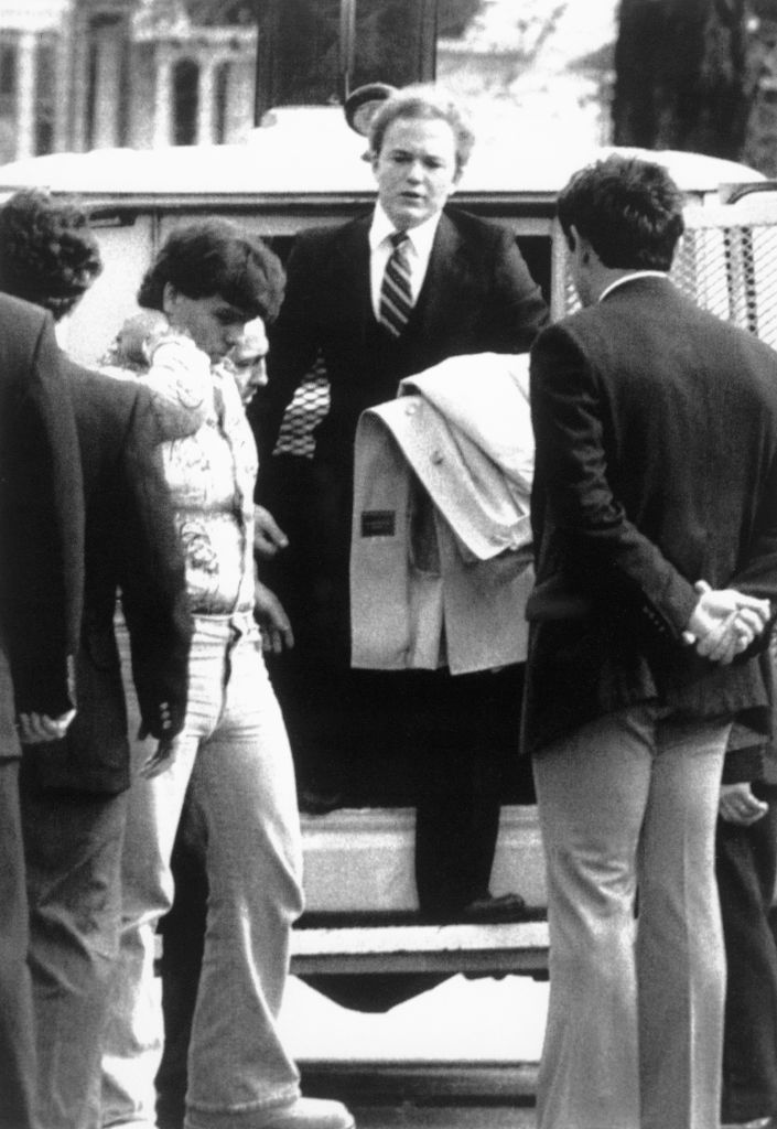 Arne C. Johnson, med jakken over armen, går ut av en politibil på vei inn i rettssalen siktet for knivdrapet på Alan Bono i Brookfield i Connecticut. Høyesterettsdommeren Robert Callahan nektet å høre på påstander om besettelse av demoner som forsvar (Bettmann Archive/Getty)